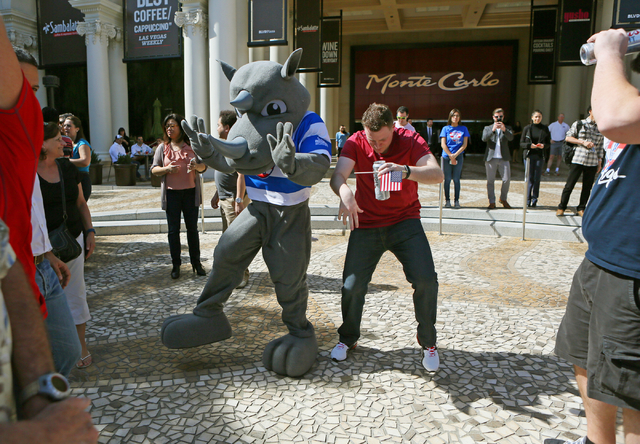 Ben Gier, right, of Chicago, dances with a mascot during a pep rally for USA Menճ Eagles Sevens Olympic rugby team outside Monte Carlo hotel-casino Wednesday, March 2, 2016, in Las Vegas. Th ...
