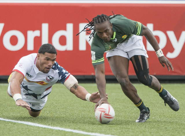United States rugby player Martin Iosefo dives for the ball as South Africa's Seabelo Senatla scores during their match in the USA Sevens rugby tournament at Sam Boyd Stadium in Las Vegas on Satur ...