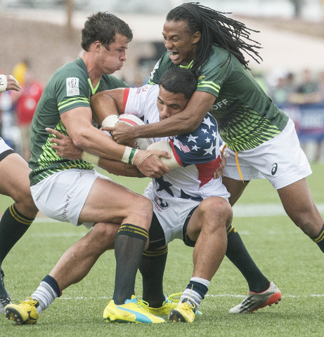 United States rugby player Martin Iosefo is stopped by South Africa's Kwagga Smith, left, and Justin Geduld during their match in the USA Sevens rugby tournament at Sam Boyd Stadium in Las Vegas o ...