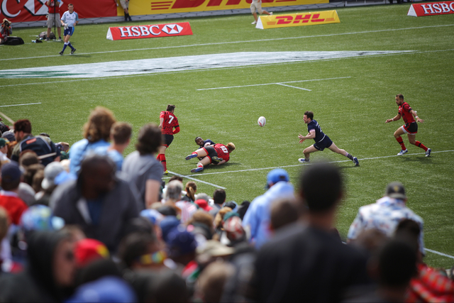 Fans look on as players chase after the ball during a game between Scotland and Wales during final day of the HSBC World Rugby Sevens Series at Sam Boyd Stadium on Sunday, March 6, 2016. Brett Le  ...