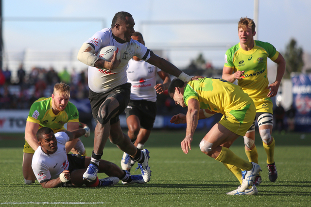Isake Katonibau (4), of Fiji, stiff-arms an Australian defender during the championship game of the HSBC World Rugby Sevens Series at Sam Boyd Stadium on Sunday, March 6, 2016. Fiji won, 21-15. Br ...