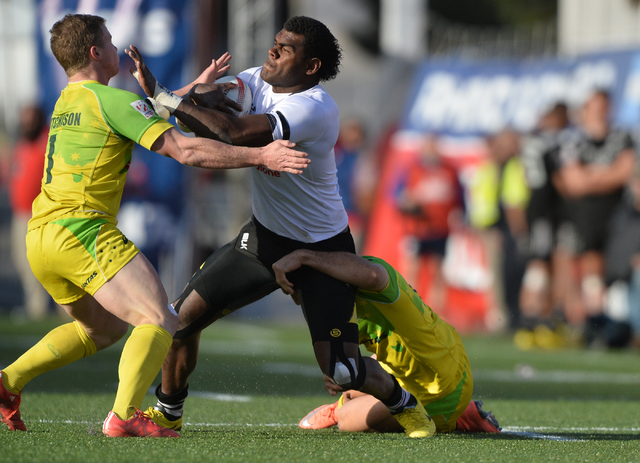 Savenaca Rawaca (11), of Fiji, drags an Australian defender while stiff-arming Henry Hutchinson (1) during the championship game of the HSBC World Rugby Sevens Series at Sam Boyd Stadium on Sunday ...