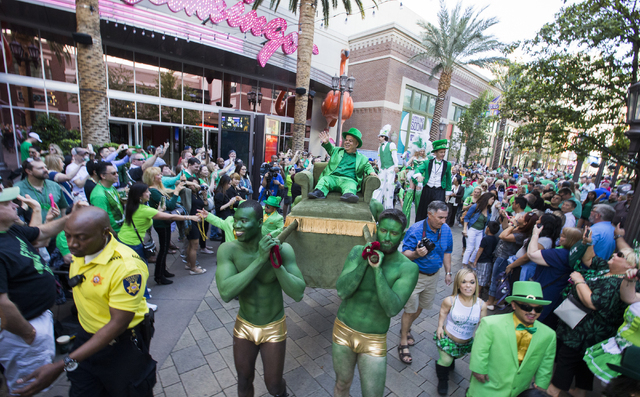 """Brian """"Lucky"""" Thomas waives to the crowd as he's carried along the parade route during in the St. Patrick's Day parade in The Linq promenade during the O'Sheas BLOQ party, Thursday, March 17, 20 ..."""