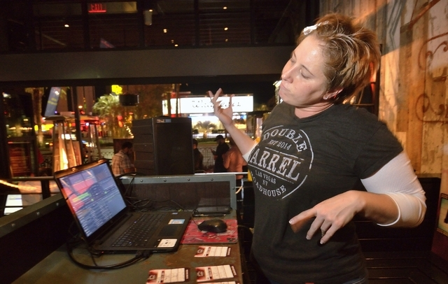 Karaoke jockey Erin Evans, aka KJ Vegas Babe, dances while keeping the songs rolling during Ҍiquid Courage KaraokeӠin the Double Barrel Roadhouse at the Monte Carlo hotel-casino at 377 ...
