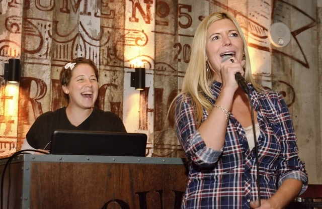Karaoke jockey Erin Evans, aka KJ Vegas Babe, left, smiles as Kris Daniels, program director and morning show host for 102.7 The Coyote, sings during Ҍiquid Courage KaraokeӠin the Doub ...