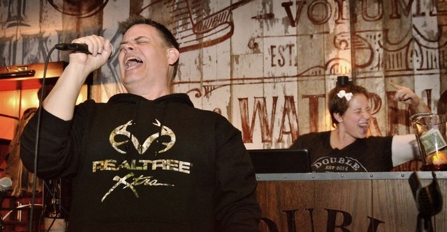 Steve Raybuck of State College, Pa., left, sings while karaoke jockey Erin Evans, aka KJ Vegas Babe, dances during Ҍiquid Courage KaraokeӠin the Double Barrel Roadhouse at the Monte Ca ...