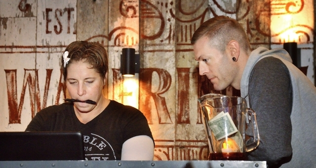 Karaoke jockey Erin Evans, aka KJ Vegas Babe, left, checks on a song for Robert Kraemer (cq) from Minneapolis during Ҍiquid Courage KaraokeӠin the Double Barrel Roadhouse at the Monte  ...