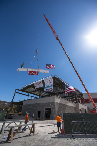 Construction workers raise the steel beam into place during the Thomas & Mack topping-off ceremony at UNLV in Las Vegas on Tuesday, March 22, 2016. Joshua Dahl/Las Vegas Review-Journal