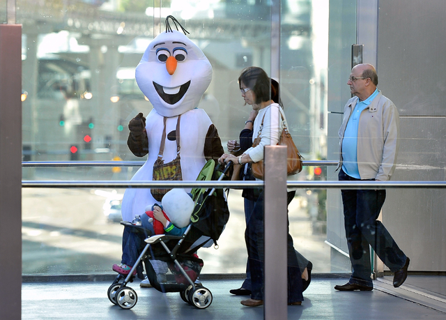 Tourists encounter a character looking for tips as they walk along a pedestrian bridge at Harmon Boulevard and the Strip in Las Vegas on Thursday, Feb. 26, 2015. David Becker/Las Vegas Review-Journal