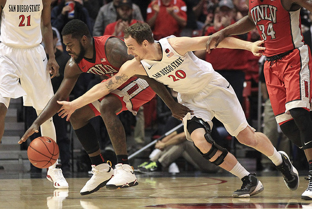 The Aztecs' Matt Shrigley, right, and UNLV's Jordan Cornish dive for a loose ball during the first half at the Viejas Arena in San Diego on Saturday. (Hayne Palmour IV/San Diego Union-Tribune, LLC)