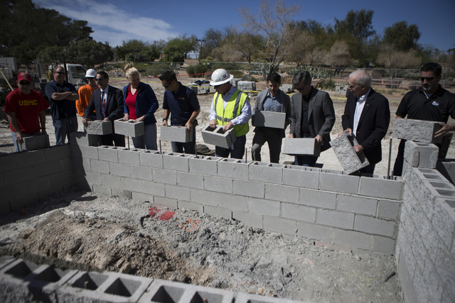Officials lay down bricks during a national tribute ceremony honoring veterans at the Las Vegas Veterans Memorial outside of the Grant Sawyer State Office Building on Saturday, March 12, 2016, in  ...