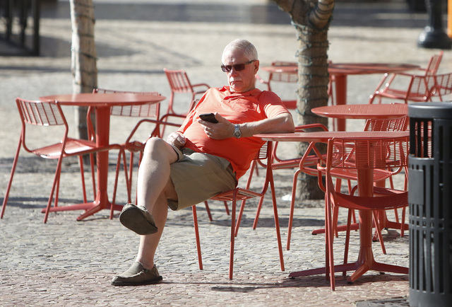 Rob Ottum checks his cellphone as he enjoys the morning sun, near MGM hotel-casino park Monday, Feb. 29, 2016, in Las Vegas. (Bizuayehu Tesfaye/Las Vegas Review-Journal Follow @bizutesfaye)