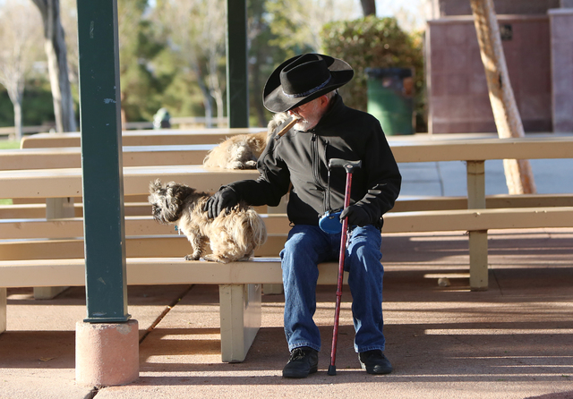 James Carlisle of Henderson enjoys his cigar as he pats his dog Tiger on a sunny morning at Vivaldi Park Tuesday, March 8, 2016, in Henderson. Bizuayehu Tesfaye/Las Vegas Review-Journal Follow @bi ...