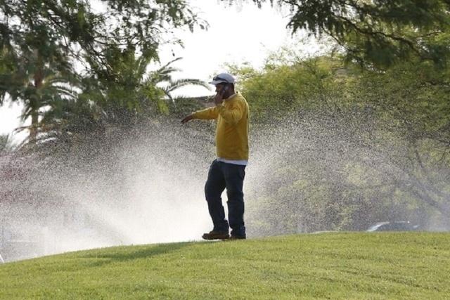 A landscaper talks on his cellphone as water sprinklers spray water at St. Rose Dominican Hospital, de Lima campus, in Henderson. (Bizuayehu Tesfaye/Las Vegas Review-Journal) Follow Bizua Tesfaye  ...