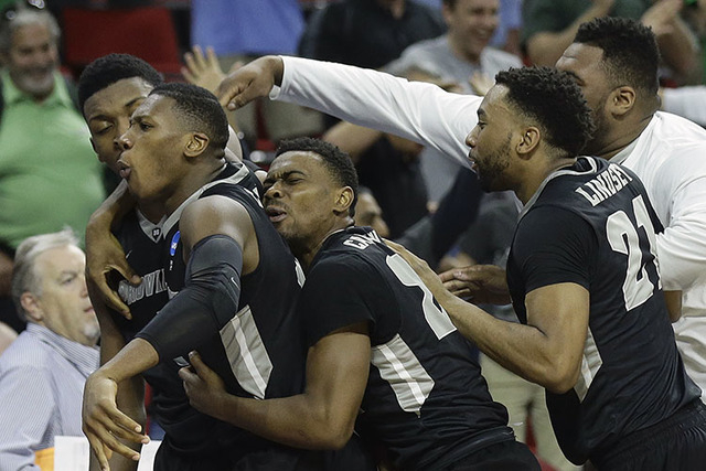 Providence forward Rodney Bullock, second from left is embraced by teammates after hitting the game-winning basket against Southern California during the second half of a first-round men's college ...