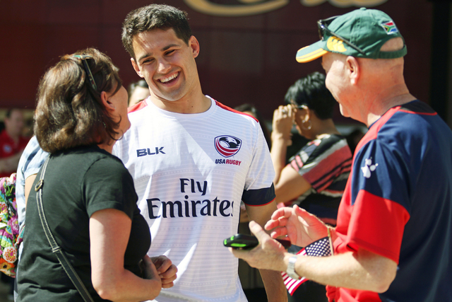 USA Men's Eagles Sevens Olympic rugby team captain Madison Hughes, center meets with fans Marcia Shand, left, and her husband Gordon, both of Denver, during a pep rally outside Monte Carlo  ...