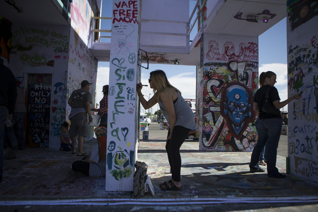 Ayasha Dunphy paints the Life Cube Project structure at the intersection of 9th Street and Fremont Street on Friday, March 25, 2016, in Las Vegas. Erik Verduzco/Las Vegas Review-Journal Follow @Er ...