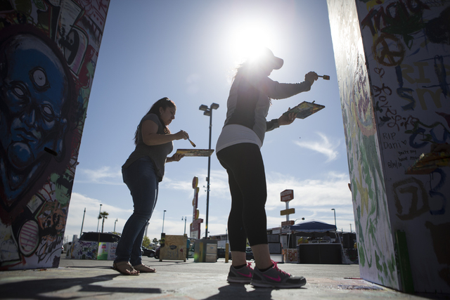 Liza Rivera, left, and Maral Saccoyah paint the Life Cube Project structure at the intersection of 9th Street and Fremont Street on Friday, March 25, 2016, in Las Vegas. Erik Verduzco/Las Vegas Re ...