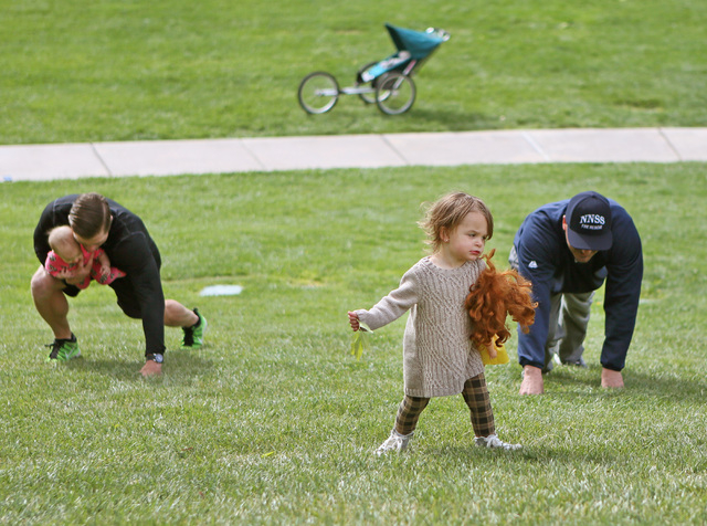 Rya Ongman, 2, walks up a hill as her father Aaron Ongman, right, and Jeff Farnham, left, holding daughter Layken, 9 months, work out at The Willows Park Tuesday, March 29, 2016, in Las Vegas. (Ro ...