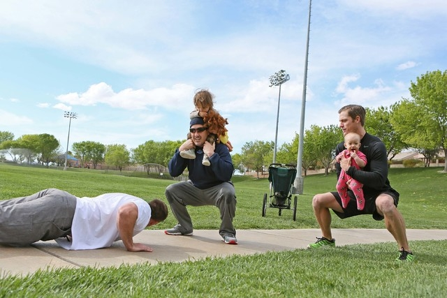 Brian Bashant, left, holds a plank position near his friends Aaron Ongman, center, holding daughter Rya, 2, and Jeff Farnham, right, holding daughter Layken, 9 months, during a workout at The Will ...