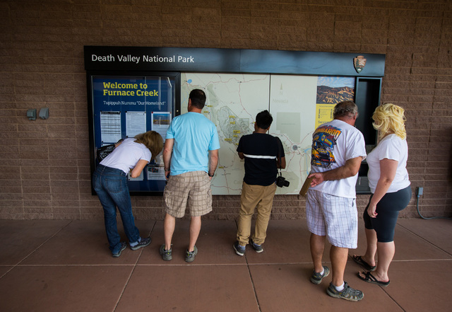 """People look at a map at the visitors center at Death Valley National Park, Calif., on Saturday, Feb. 27, 2016. The National Park Service said in a statement that the """"current bloom in Death Valley ..."""