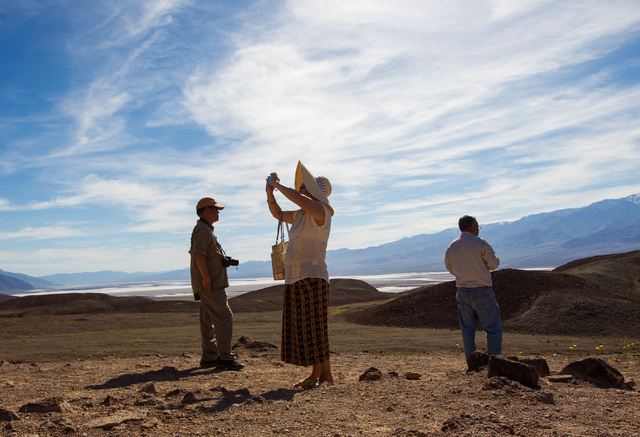 Bailing Zhang of Palos Verdes, Calif., center, takes a photo as Herman Pang, left, and Felix Pang look on during a stop along Artists Drive in Death Valley National Park, Calif. on Saturday, Feb.  ...