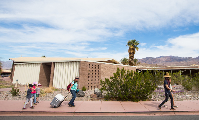"""People walk outside of the visitors center at Death Valley National Park, Calif., on Saturday, Feb. 27, 2016. The National Park Service said in a statement that the """"current bloom in Death Valley  ..."""