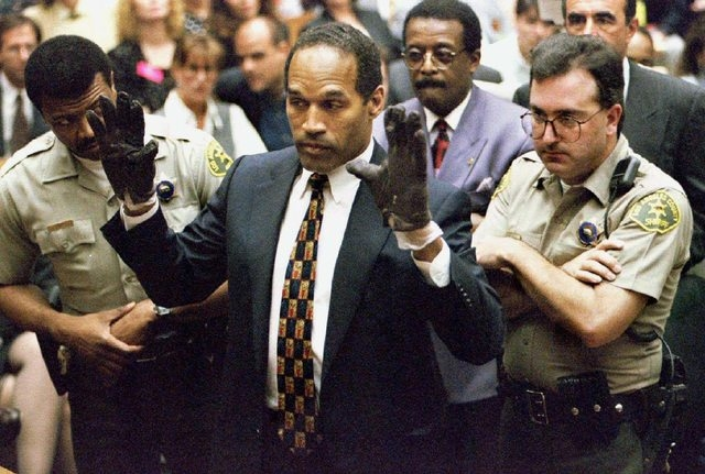 O.J. Simpson holds up his hands to the jury showing leather gloves that prosecutors say he wore the night of the murders of his ex-wife Nicole Brown Simpson and Ron Goldman during the Simpson doub ...