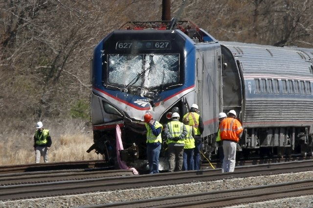 Emergency personnel examine the scene after an Amtrak passenger train struck a backhoe, killing two people, in Chester, Pennsylvania, April 3, 2016. The southbound Palmetto train running from New  ...