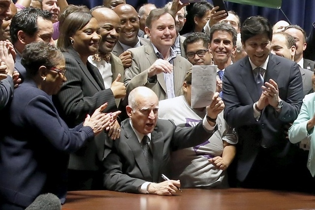 California Governor Jerry Brown (C) signs a bill hiking California's minimum wage to $15 by 2023 in Los Angeles, California, United States, April 4, 2016. (REUTERS/Lucy Nicholson)