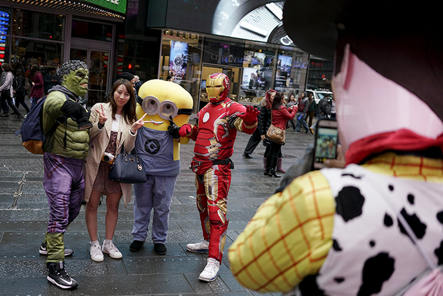 A tourist (2nd L) poses with two people dressed as Hulk and Iron Man, as another dressed as Woody from Toy Story takes their photo in Times Square, in New York, April 7, 2016.  REUTERS/Rickey Rogers