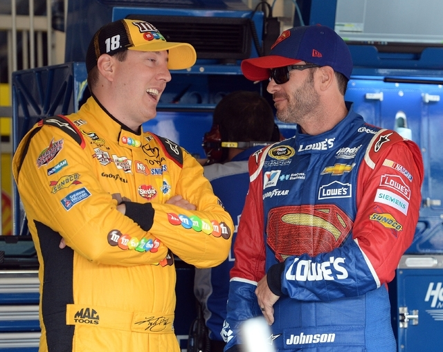 Kyle Busch, left, speaks with Jimmie Johnson in the garage area prior to the opening practice session Friday, March 18, 2016, for the NASCAR auto race at Auto Club Speedway in Fontana, Calif. (Wil ...