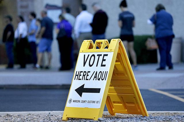 Voters wait in line at dawn to cast their ballot. (AP Photo/Matt York)