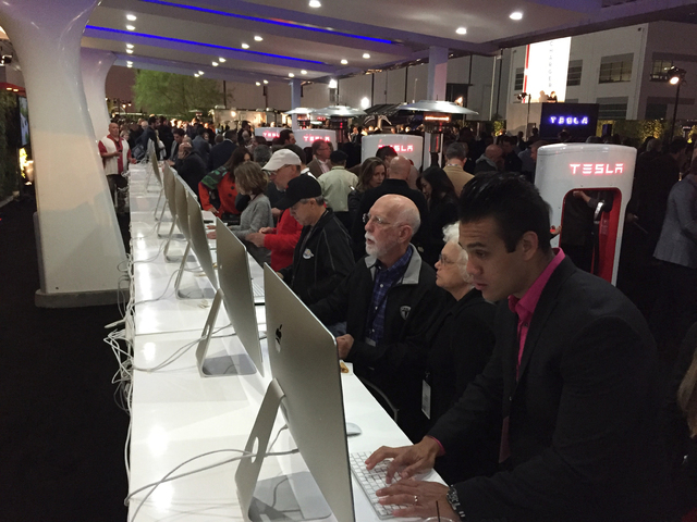 People sit at computers where they can reserve one of the cars before Tesla Motors unveils the Model 3 at the Tesla Motors design studio Thursday, March 31, 2016, in Hawthorne, Calif. The promise  ...