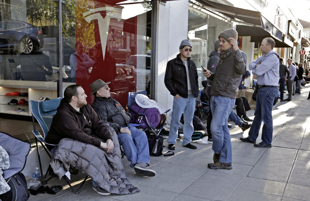 Nick Tobin, left, with his father, Byron Tobin, second from left, wait in line to be the first to sign a wait list to own the new Tesla Model 3 at the Tesla showroom in Pasadena, Calif., Thursday, ...