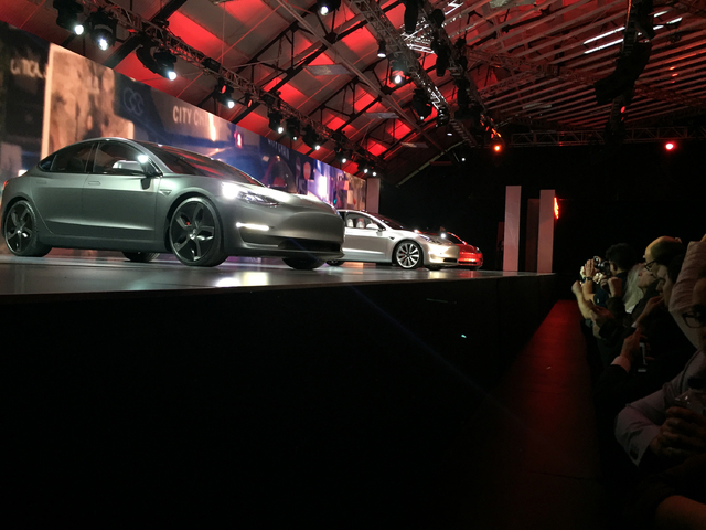 Tesla Motors unveils its Model 3 car at the Tesla Motors design studio Thursday, March 31, 2016, in Hawthorne, Calif. The promise of an affordable electric car from Tesla Motors had hundreds of pe ...