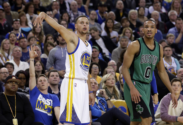 Golden State Warriors' Stephen Curry (30) makes a 3-point basket next to Boston Celtics' Avery Bradley (0) during the first half of an NBA basketball game Friday, April 1, 2016, in Oakland, Calif. ...