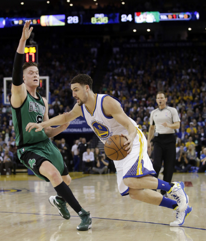 Golden State Warriors' Klay Thompson (11) dribbles next to Boston Celtics' Jonas Jerebko (8) during the first half of an NBA basketball game Friday, April 1, 2016, in Oakland, Calif. (AP Photo/Mar ...