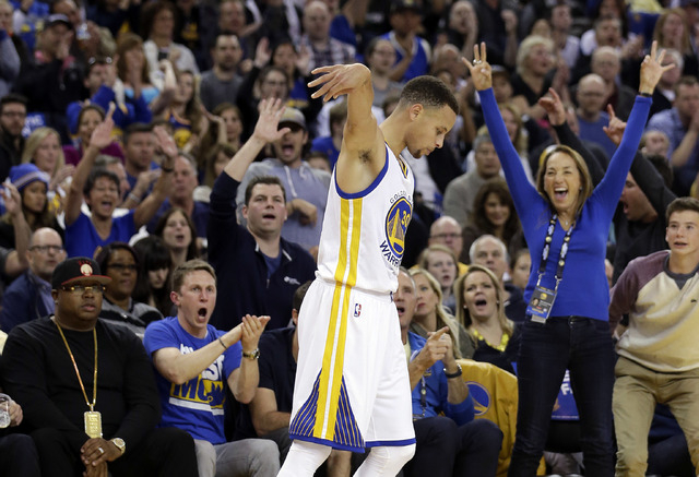 The crowd reacts after Golden State Warriors' Stephen Curry, center, made a 3-point basket during the first half of an NBA basketball game against the Boston Celtics on Friday, April 1, 2016, in O ...