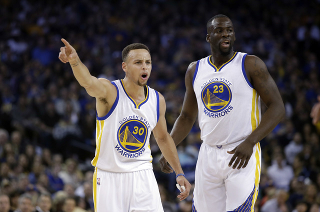 Golden State Warriors' Stephen Curry (30) argues a call next to teammate Draymond Green (23) during the first half of an NBA basketball game against the Boston Celtics on Friday, April 1, 2016, in ...