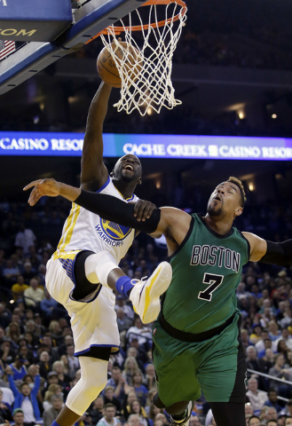 Golden State Warriors' Draymond Green, left, is fouled while driving to the basket by Boston Celtics' Jared Sullinger (7) during the first half of an NBA basketball game Friday, April 1, 2016, in  ...