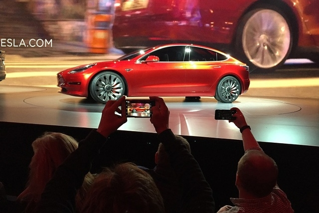 Tesla Motors unveils the new lower-priced Model 3 sedan at the Tesla Motors design studio in Hawthorne, Calif., Thursday, March 31, 2016. (AP Photo/Justin Pritchard)