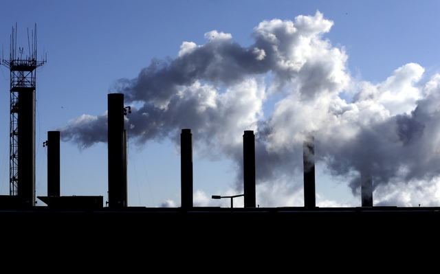 FILE - This Jan. 7, 2015, file photo, shows factory chimneys near O'Hare International Airport in Chicago. On Monday, April 4, 2016, the Commerce Department reports on U.S. factory orders for Febr ...