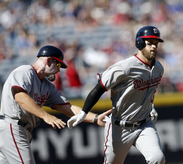 Washington Nationals' Bryce Harper), right, is greeted by third base coach Bob Henley, left, after hitting a solo-home run in the first inning of a baseball game against the Atlanta Braves, Monday ...