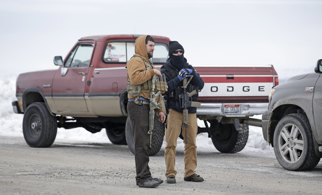 "In this Jan. 9, 2016 file photo, men stand guard after members of the ""3% of Idaho"" group and several other organizations arrived at the Malheur National Wildlife Refuge, near Burns, Ore. (Rick Bo ..."