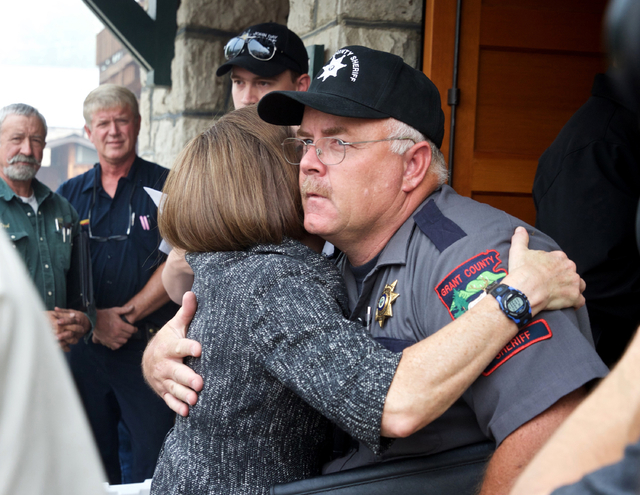 In this Aug. 19, 2015 file photo, Oregon Gov. Kate Brown hugs Grant County Sheriff Glenn Palmer as they enter a meeting with homeowners in Canyon City, Ore. (Thomas Boyd /The Oregonian via AP, File)