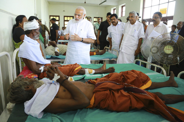 Indian Prime Minister Narendra Modi, center, visits the injured victims at the Kollam district hospital after a massive fire broke out during a fireworks display at the Puttingal temple complex in ...