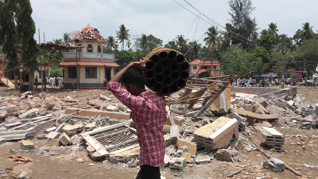A man walks carrying empty shells of fireworks past a collapsed building after a massive fire broke out during a fireworks display at the Puttingal temple complex in Paravoor village, north of Thi ...