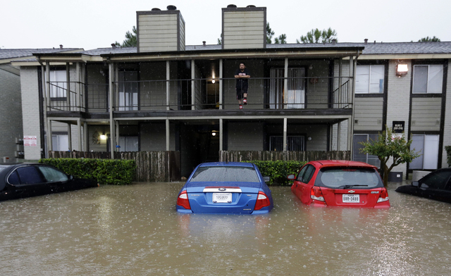 A resident looks out from the second floor as floodwaters surround his apartment complex Monday, April 18, 2016, in Houston. Storms have dumped more than a foot of rain in the Houston area, floodi ...