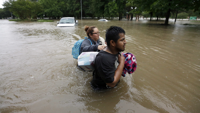 Margarita Uribe, left, and her husband, Juan Juarez, wade through floodwaters as they evacuate their flooded apartment complex Monday, April 18, 2016, in Houston. Storms have dumped more than a fo ...